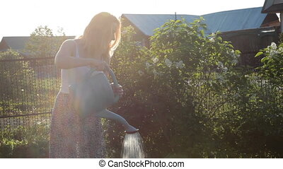 Woman watering sunny garden with watering can - Smiling...