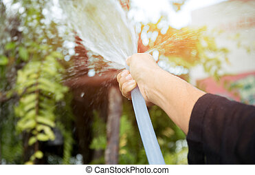 Woman watering the garden with garden hose water