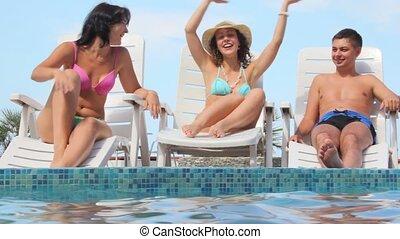 woman waving hands sits on deck chair near water pool, friends has fun
