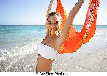 Woman waving kerchief on the beach
