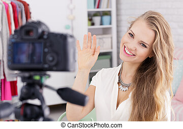 Woman waving to camera - Young woman with necklace smiling...