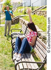 Woman waving to man sitting on bench