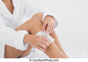 Woman waxing leg at spa center - Close up of a woman waxing...