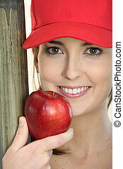 woman wearing a cap and eating an apple
