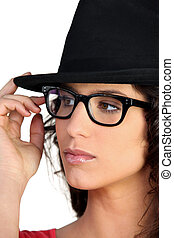Woman wearing a hat and thick-framed glasses