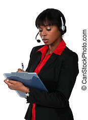 Woman wearing a headset and writing on a clipboard