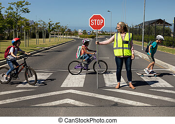Front view of a blonde Caucasian woman wearing a high visibility vest and holding a stop sign, standing in the road, turning to the side while three schoolchildren ride bicycles and a skateboard on a pedestrian crossing, stopping the traffic while they cross the street safely on their way to ...