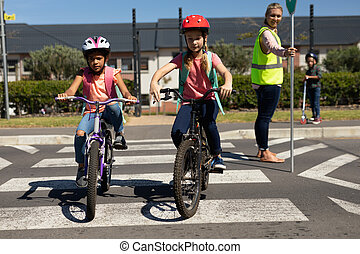 Side view of a blonde Caucasian woman wearing a high visibility vest and holding a stop sign, standing in the road on a pedestrian crossing and stopping the traffic while a Caucasian and an African American schoolgirl ride their bicycles across the road safely on their way to elementary school