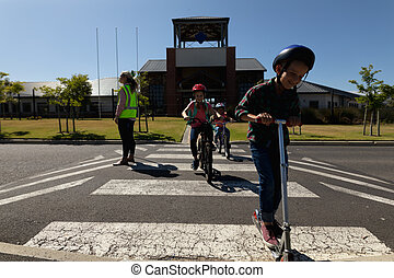 Side view of a blonde Caucasian woman wearing a high visibility vest and holding a stop sign, standing in the road on a pedestrian crossing and stopping the traffic while a Caucasian boy riding a push scooter, and an African American and a Caucasian schoolgirl riding bicycles cross the road safely ...