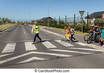 Front view of a blonde Caucasian woman wearing a high visibility vest walking on a pedestrian crossing and turning to face a diverse group of schoolchildren, on a scooter, bicycles and walking, stopping the traffic while the children cross the street safely on their way to elementary school