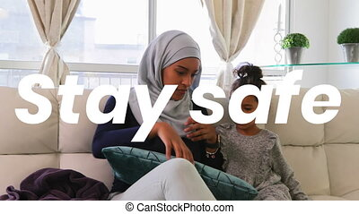 Woman wearing a hijab with her daughter at home during ...