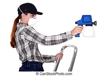 Woman wearing a mask to use a spraygun