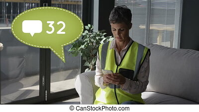 Close up of a Caucasian female worker wearing a safety vest seated on a couch while texting on her phone. Beside her in the foreground is a message bubble with a message icon and a number count up