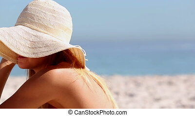 Woman wearing a straw hat and sitting on the beach under a...