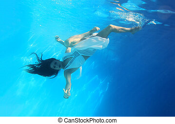 Woman wearing a white dress underwater in swimming pool
