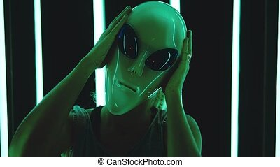 Portrait of caucasian blonde straight hair woman wearing an alien mas - surreal, eccentric concept