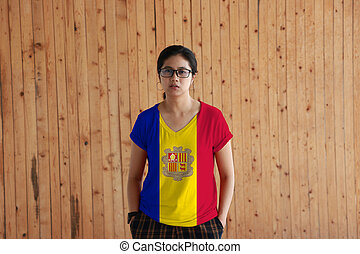 Woman wearing Andorra flag color shirt and standing with two hands in pant pockets on the wooden wall background.