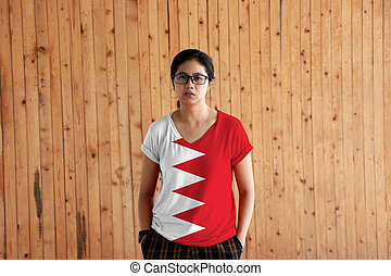 Woman wearing Bahrain flag color shirt and standing with two hands in pant pockets on the wooden wall background.