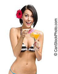 Woman wearing bikini and flower in hair drinks cocktail -...