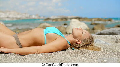 Woman Wearing Bikini Suntanning on Sandy Beach