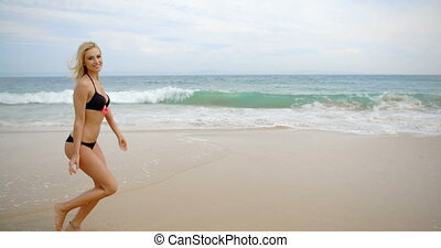Woman Wearing Black Bikini Running on Beach