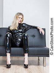 woman wearing black extravagant clothes and pumps sitting on...