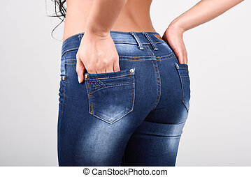 Woman wearing blue jeans with a beautiful waist. Studio shot