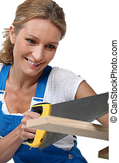 Woman wearing blue overalls sawing plank of wood