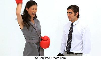 Woman wearing boxing gloves alongside her colleague