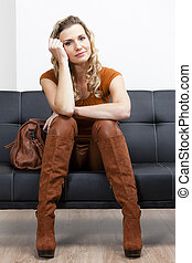 woman wearing brown clothes and boots with a handbag sitting on sofa