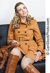 woman wearing brown coat sitting on sofa