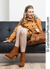 woman wearing brown coat with a handbag sitting on sofa