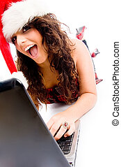 woman wearing christmas hat and working on laptop