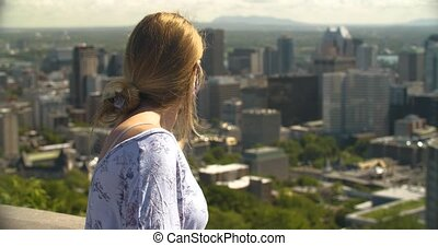 Lonely young woman wearing covid-19 face protection mask looking at silent city due to coronavirus pandemic from observatory horizon view