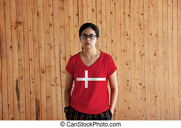 Woman wearing Denmark flag color shirt and standing with two hands in pant pockets on the wooden wall background.