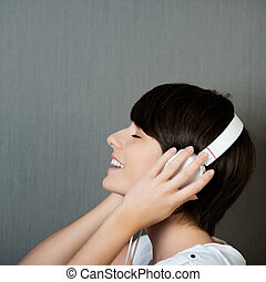 Profile head and shoulders portrait of a beautiful smiling young woman wearing earphones listening to music