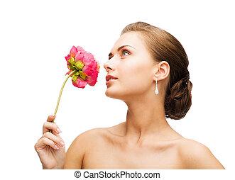 woman wearing earrings and smelling flower