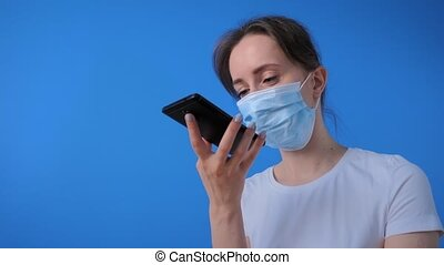 Authentication, quarantine, self isolation concept. Woman in medical face mask holding smartphone device, using voice recognition function, recording audio message, talking with mobile assistant