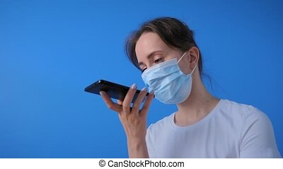 Woman in medical face mask holding smartphone device, using voice recognition function, recording audio message, talking with mobile assistant. Authentication, quarantine, self isolation concept