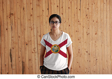 Woman wearing Florida flag color shirt and standing with two hands in pant pockets on the wooden wall background, the states of America.