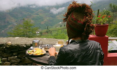 Woman wearing funny hat eating breakfast at himalayas mountain, Nagarkot, Kathmandu, Nepal