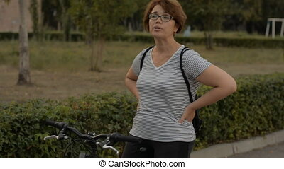 Woman wearing glasses on a bicycle in the park in the...