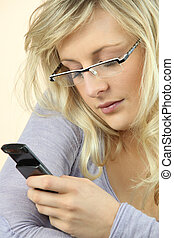 Woman wearing glasses sending a text message
