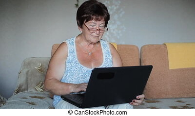 Woman wearing glasses sitting on a sofa at home concentrating as she works on a laptop