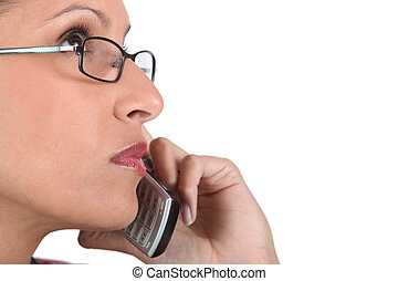 Woman wearing glasses using telephone