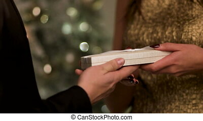 Woman wearing gold dress, opening little white box gifted by her caring boyfriend.