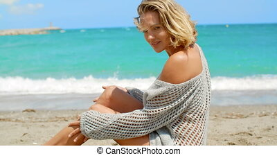 Woman Wearing Grey Sweater Sitting on Sandy Beach - Blond...