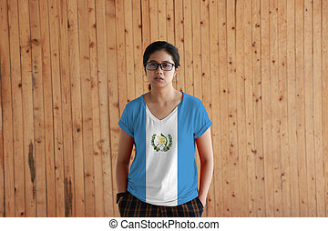 Woman wearing Guatemala flag color shirt and standing with two hands in pant pockets on the wooden wall background, blue and white color with the national Emblem centered.