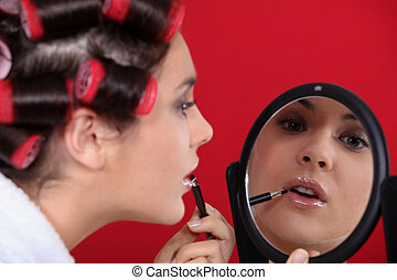 Woman wearing hair rollers applying make-up