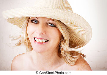 Beautiful middle aged woman wearing a sun hat and smiling.